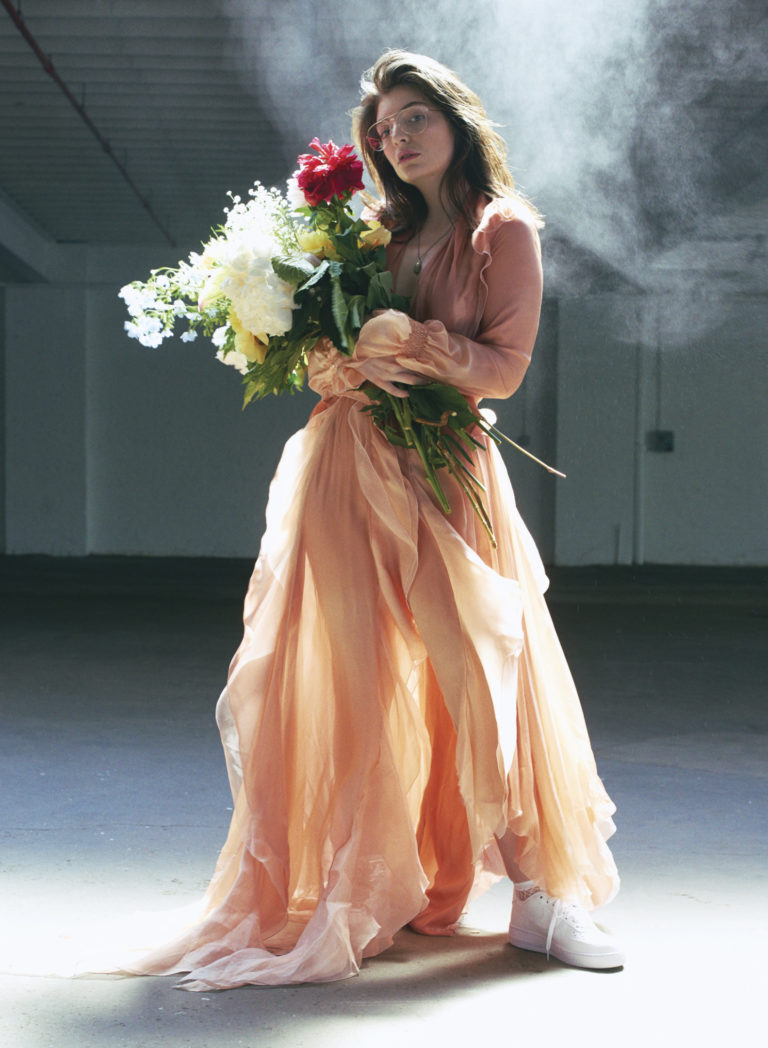 Lorde in a dress holding flowers FASHION Magazine