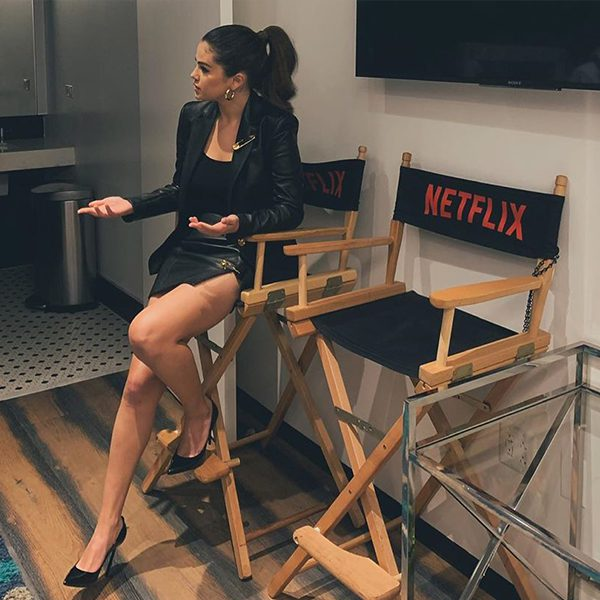 Selena Gomez sitting in a Netflix director chair